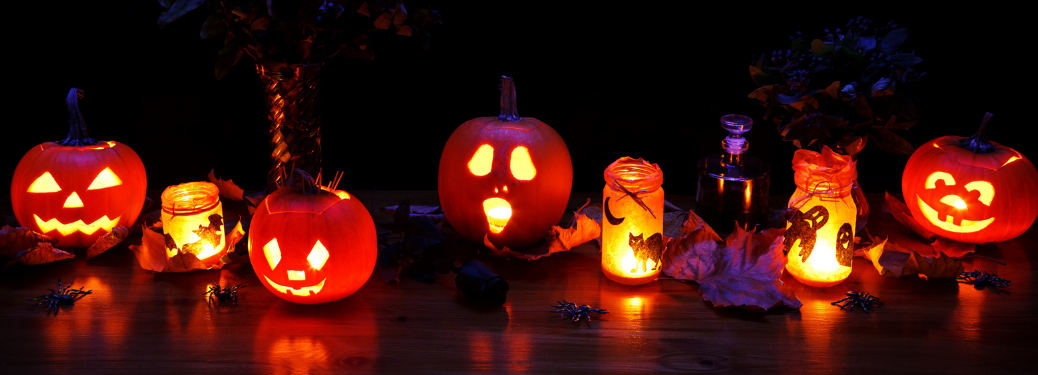 A row of Halloween decorations and Jack-O'-Lanterns on a table