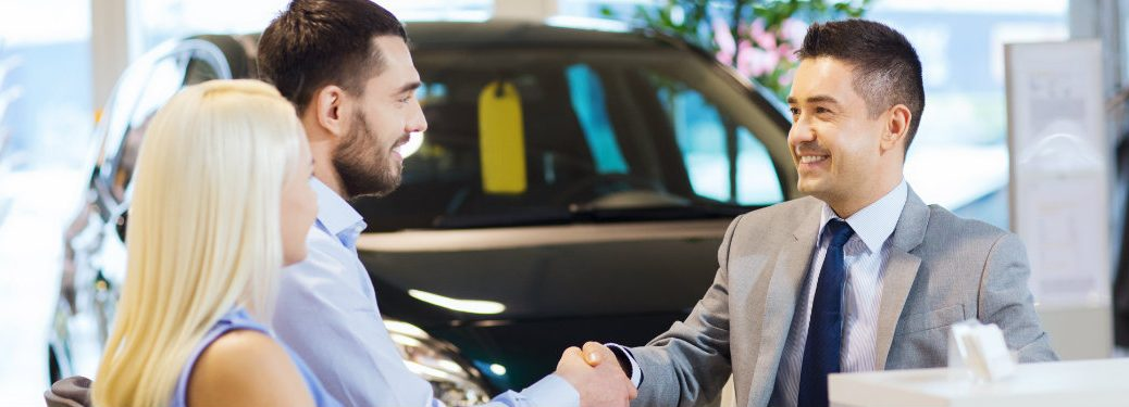 car salesman shaking hands with with a couple after a sale