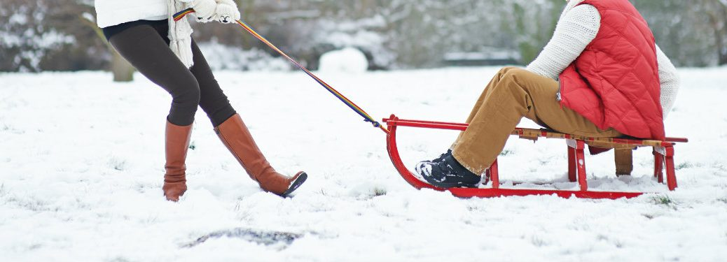 couple laughing, a woman pulling a man on a sled