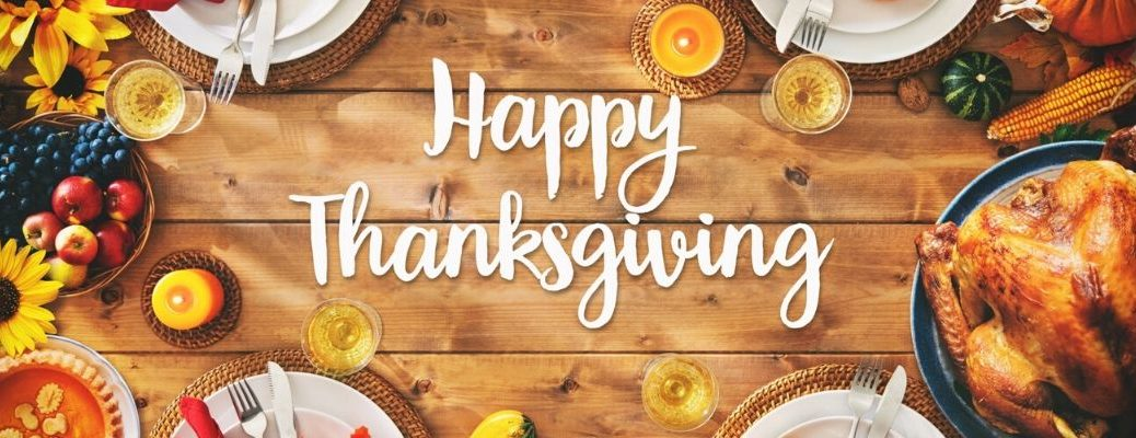 Happy Thanksgiving banner with traditional Thanksgiving food on a wooden table