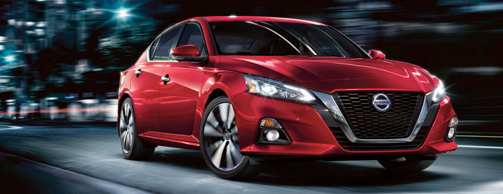 Front view of red 2020 Nissan Altima speeding on city road
