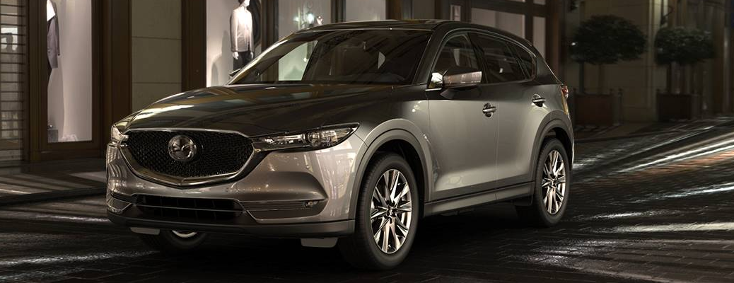 2019 Mazda CX-5 exterior shot with sonic silver metallic paint color parked on a stone tile path at night near a fancy clothing store