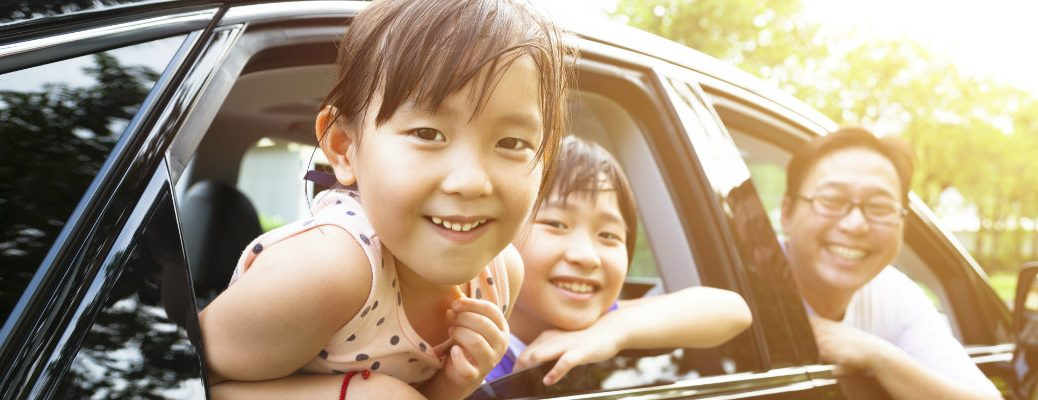 A happy girl and brother and father smiling out car windows