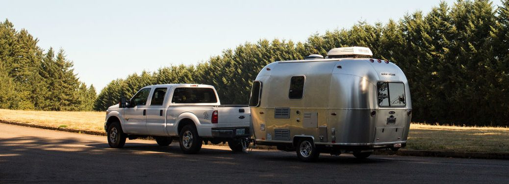 2019 Airstream Sport exterior back and left side pulled by pickup truck on road with pine trees