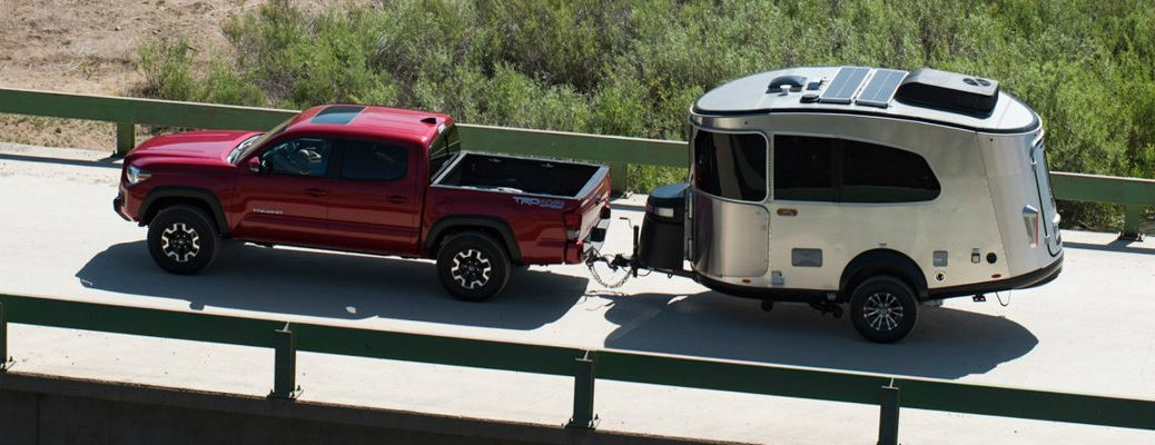 Toyota Tacoma TRD Pro pickup truck towing a 2020 Airstream Basecamp small trailer over a bridge