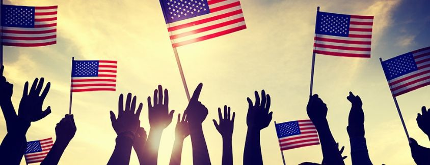 Image of people holding their hands up in the air with small American Flags