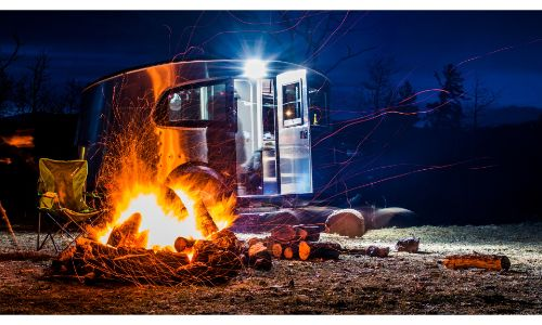 2020 Airstream Basecamp parked in front of campfire at night long exposure