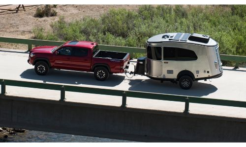 2020 Airstream Basecamp pulled by red pickup over bridge