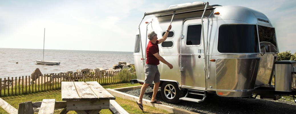 A 2020 Airstream Caravel RV set up next to a large lake.