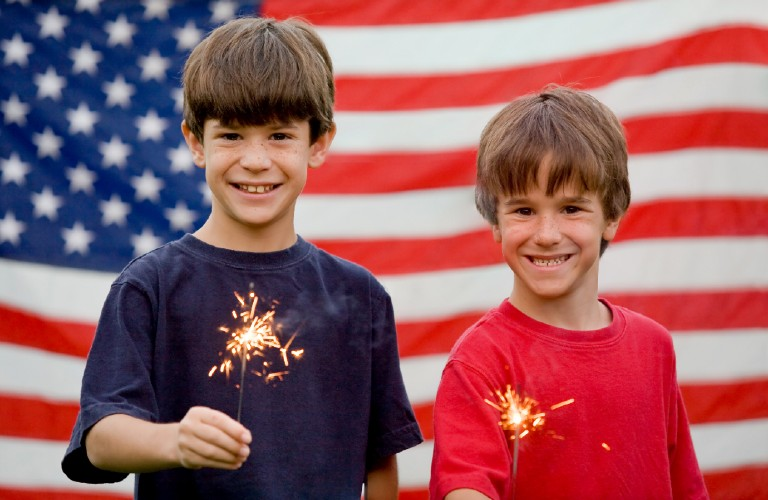 Two boys standing in front of an American flag smiling with sparklers in their hand.