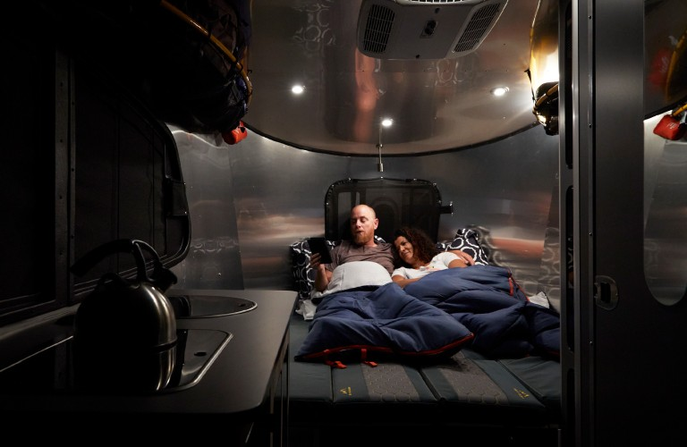 A young couple laying in the rear dinette bed area at night inside a 2021 Airstream Basecamp 20.