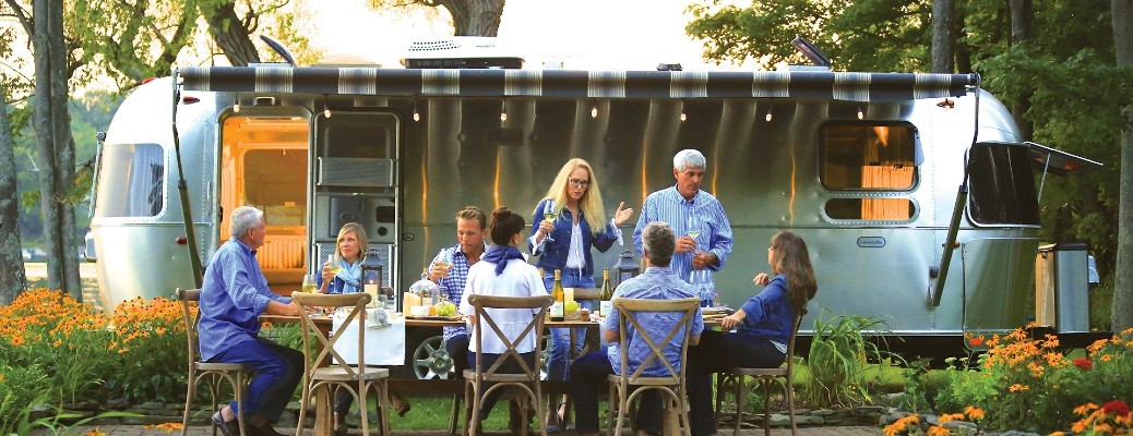 A family sitting down for a meal in front of a 2021 Airstream Globetrotter.