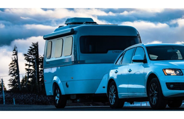 A 2020 Audi Q3 towing a 2020 Airstream Nest at dusk.