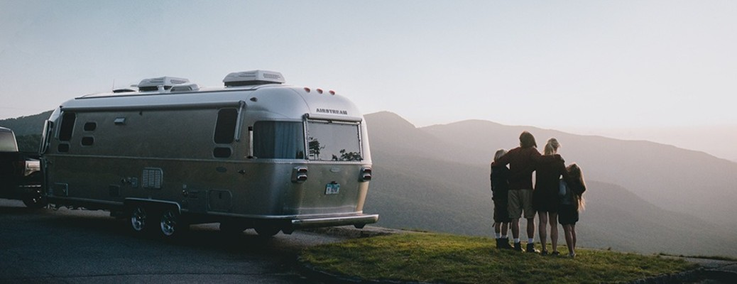 A family standing together near a 2021 Airstream Flying Cloud.