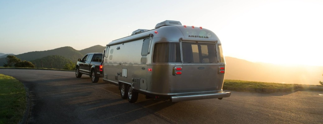 The rear and side view of a truck hauling a 2021 Airstream Flying Cloud.