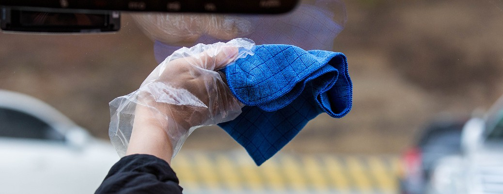 hand with plastic glove cleaning windshield inside with blue rag