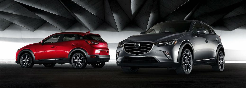 Exterior side view of a red 2018 Mazda CX-3 in the background and a front exterior view of a gray 2018 Mazda CX-3 in the foreground
