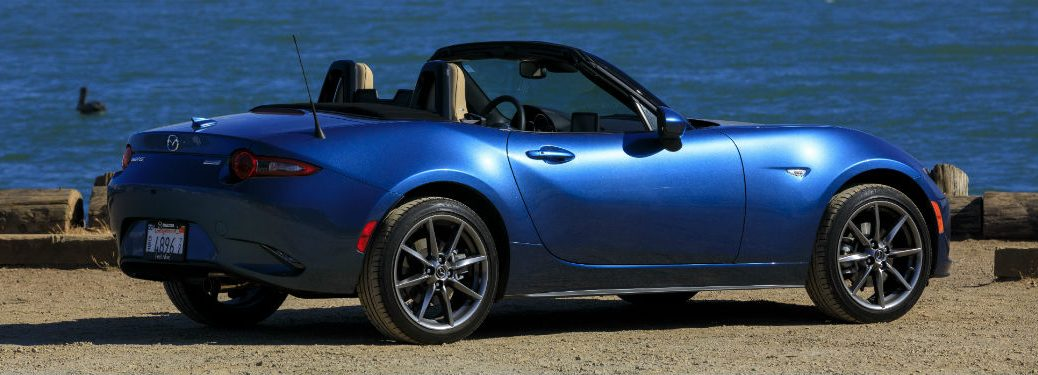 Passenger side exterior view of a blue 2019 Mazda MX-5 Miata with the top down