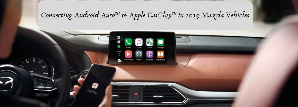 Connecting Android Auto™ & Apple CarPlay™ in 2019 Mazda Vehicles, text on an image of a driver connecting to the color touchscreen display in their Mazda using Apple CarPlay™