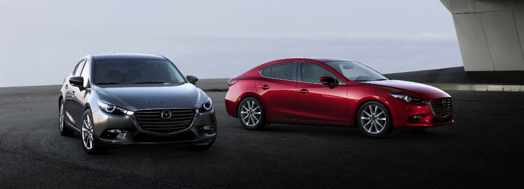 Front exterior view of a gray 2018 Mazda3 5-Door parked to the left of a driver side exterior view of a red 2018 Mazda3 4-Door