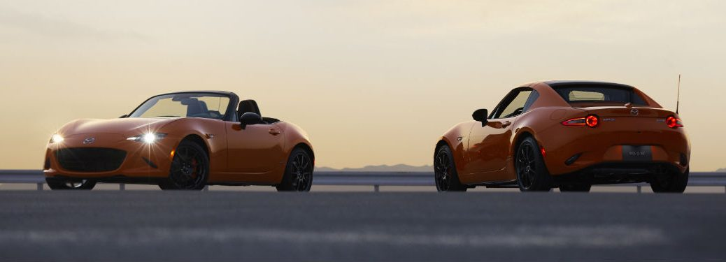 Front exterior view of an orange 30th Anniversary Mazda MX-5 Miata soft top on the left parked next a rear exterior view of an orange 30th Anniversary Mazda MX-5 Miata RF on the right