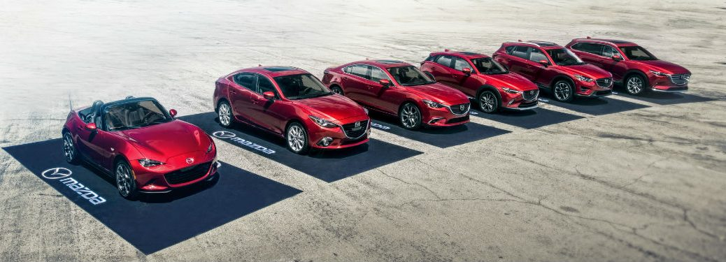 """The full 2019 Mazda vehicle lineup parked in the desert on black """"Mazda"""" parking pads"""