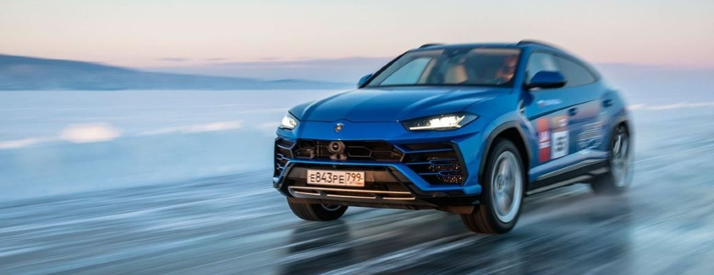 The front and side view of a blue Lamborghini Urus driving on ice.