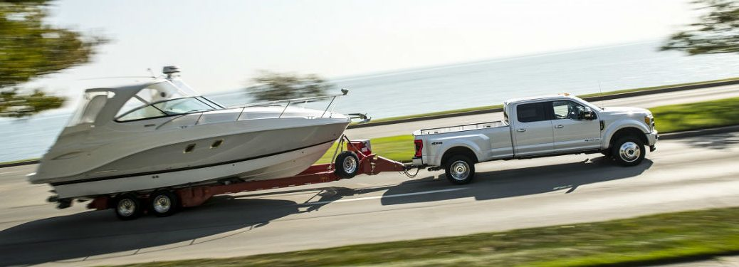 2018 Ford Super Duty In White Pulling Boat Up A Steep Hill Near Coast