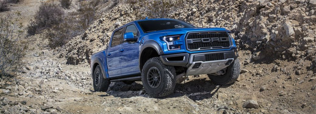 2019 Ford Raptor enjoying outdoor activities by climbing rocks and shot at one quarter front passenger