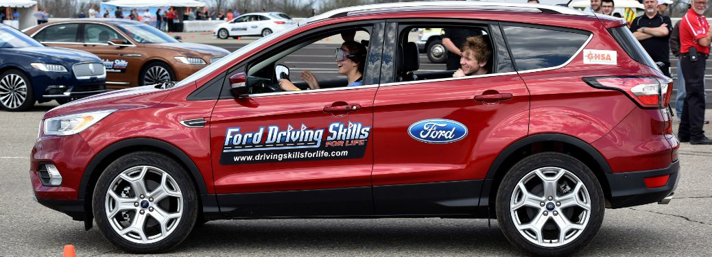 Teenagers in a red Ford Escape with a Ford Driving Skills for Life logo