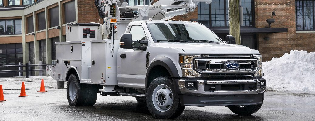 White 2021 Ford F-600 Super Duty Chassis Cab parked in front of a large brick building