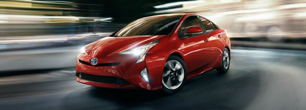 red 2018 Toyota Prius driving down the street