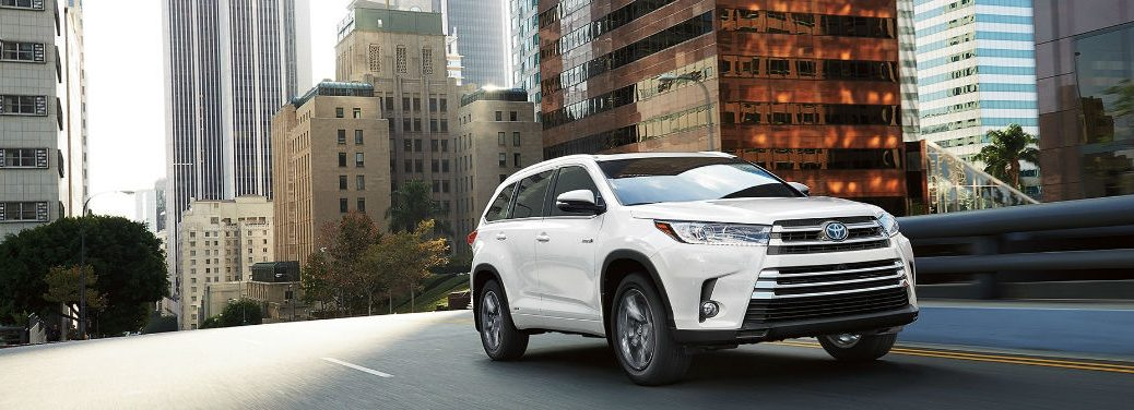 2018 Toyota Highlander and Highlander Hybrid Praised for Fuel Efficiency with image of a 2018 Highlander Hybrid Limited driving in a city