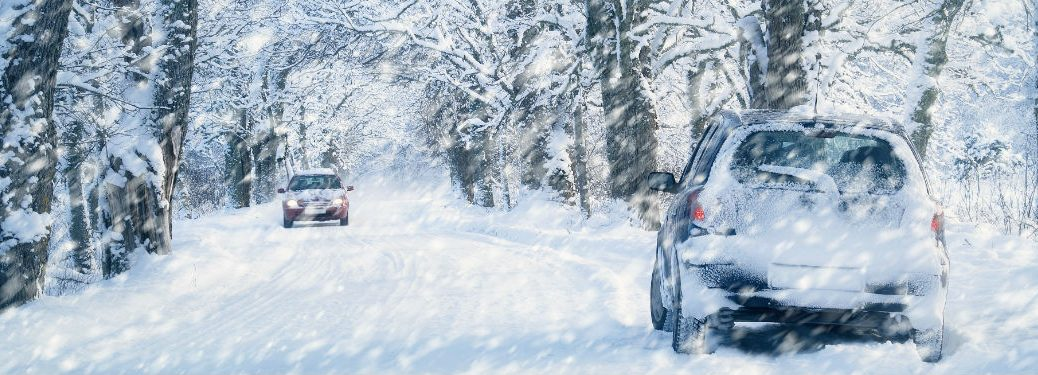 10 Tips for Driving on Snow and Ice with image of 2 cars driving in a snow storm