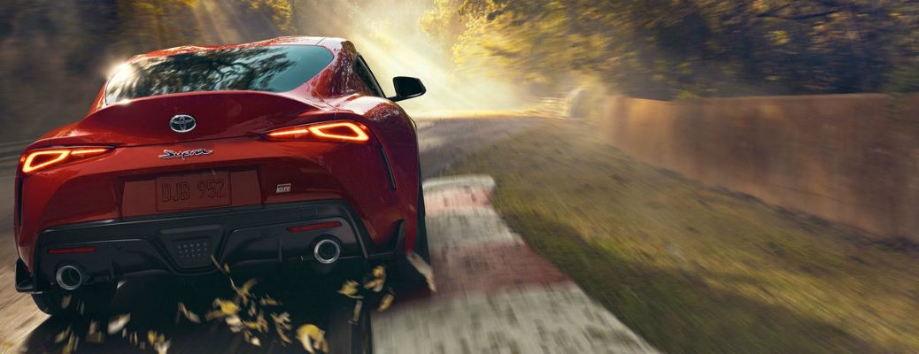 Red 2020 Toyota Supra driving down a road