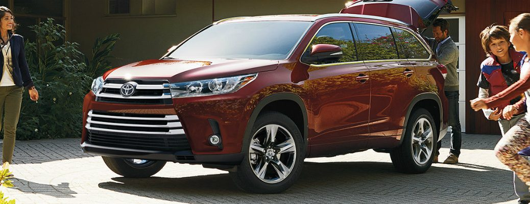Family getting ready to hit the road in a red 2019 Toyota Highlander