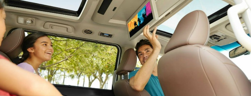 Father setting up the entertainment system in the Toyota Sienna