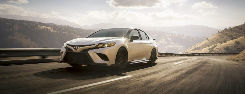 White 2020 Toyota Camry cruising down a highway