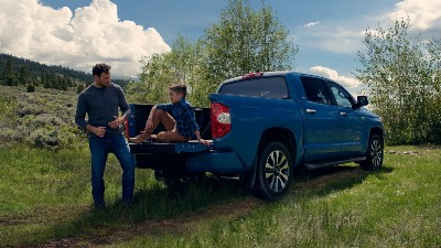 2021 Toyota Tundra exterior rear fascia boy sitting in tailgate with father standing in front in grass