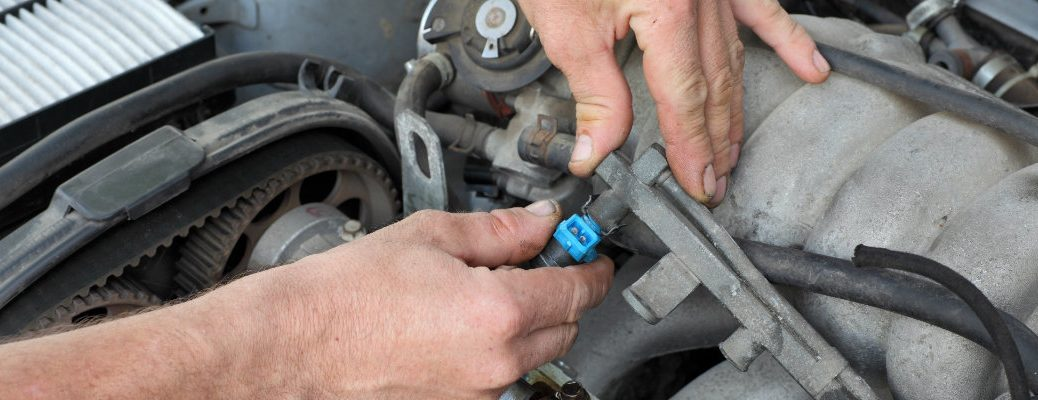 Someone working on the fuel injector of a vehicle