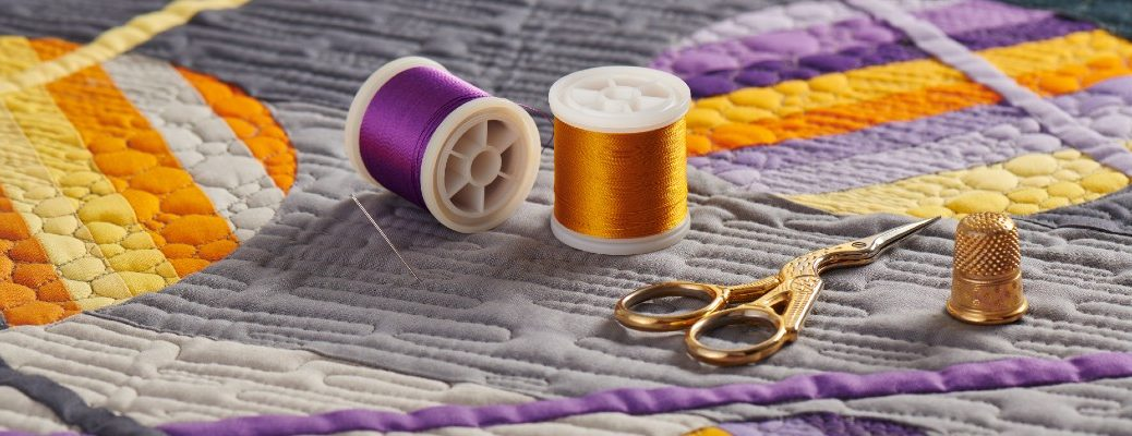 Purple and orange thread spools and thread scissors on a finished quilt