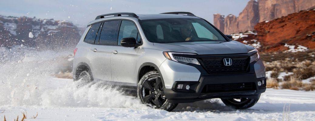 2021 Honda Passport Front Right Quarter View drifting in snow with mountains in the background.