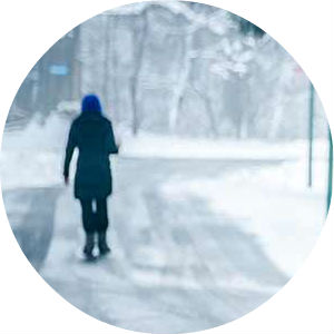 Woman Walking on a Snow-Covered Road