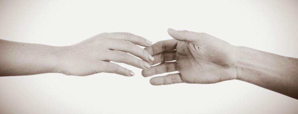 A sepia-toned photo of two hands reaching for one another