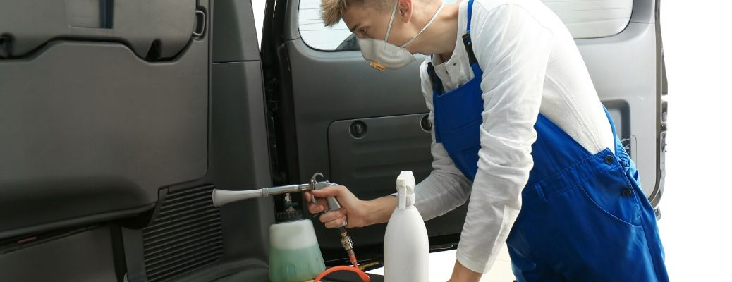 Man cleaning interior of vehicle