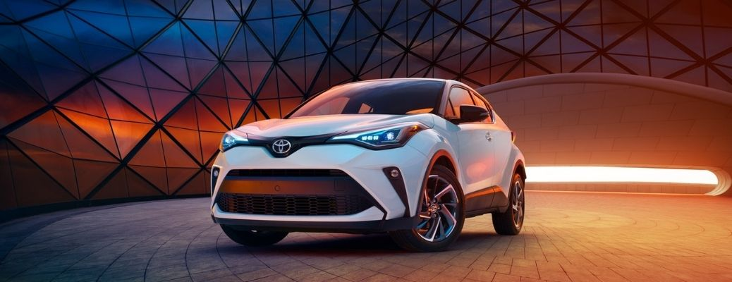 front view of the 2021 Toyota C-HR behind which there is yellow and orange light