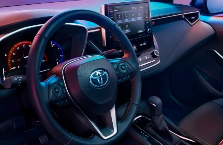 The steering wheel and dashboard of the 2022 Toyota Corolla.