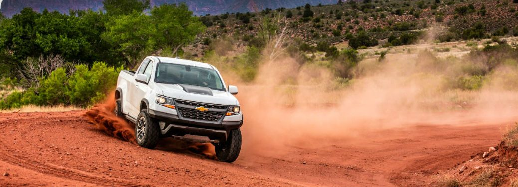 2018 chevy colorado in white zipping around dusty old sand dunes