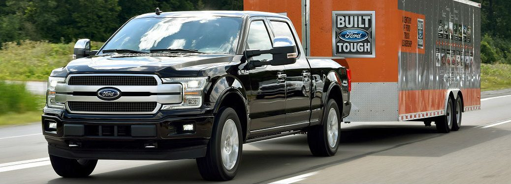 2018 ford f-150 towing a large trailer behind it with the words ford on it near scottsboro al