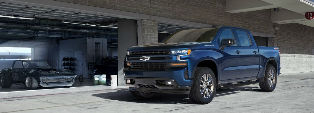 2019 Chevrolet Silverado mid trim level parked in front of airport or industrial type garage
